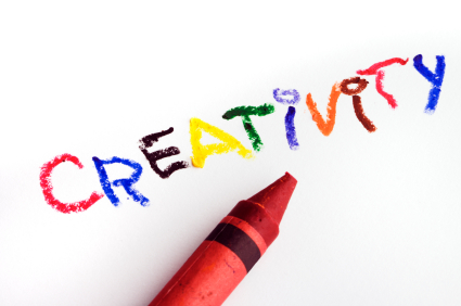 The word creativity is written in rainbow colors in crayon