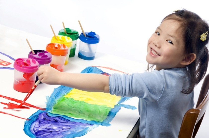 Little girl smiling and painting a picture