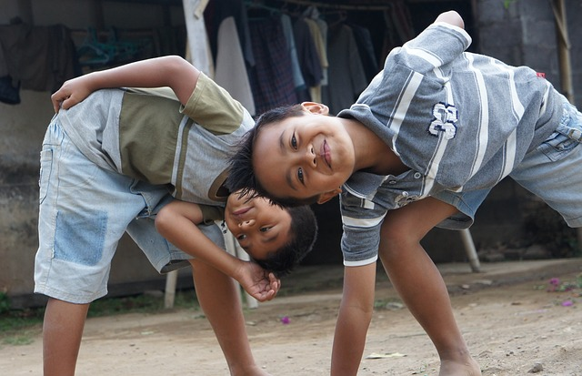 Two young boys acting silly in a street scene.