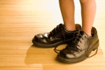 Big shoes to fill, child's feet in large black shoes, on wood fl