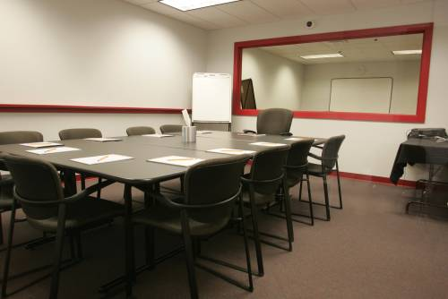 A focus group discussion room; the mirror framed in red hides a viewing room