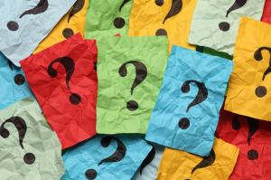Crumpled colorful paper notes with question marks.