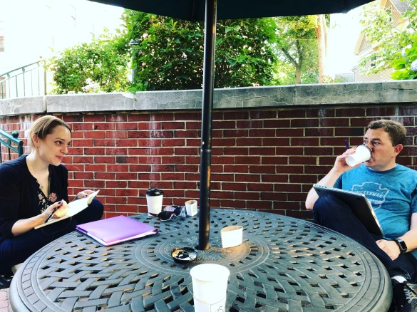 Two writers discussing their work at an outdoor table.